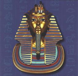 Descripción: Reproducción a tamaño real de la Máscara funeraria de Tutankhamón | Pieza de oro con incrustaciones de lapislázuli que estaba colocada directamente de la momia del rey, cubriendo la cabeza y parte de los hombros. Se aprecian en la máscara el tocado Nemes (especie de pañuelo a rayas) con las Diosas Nejbet y Uadyet - representadas como buitre y cobra -, que protegían al faraón en su sepulcro, y la barba postiza trenzada.